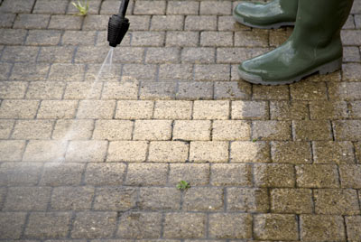A person in boots using a pressure washer to clean concrete