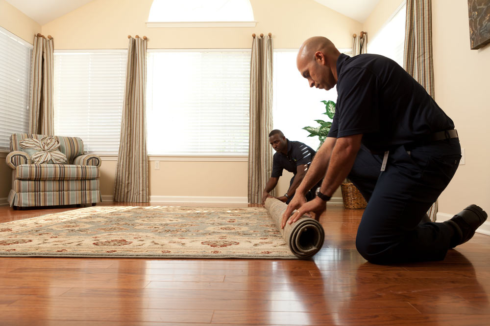 Two technicians roll an area rug.