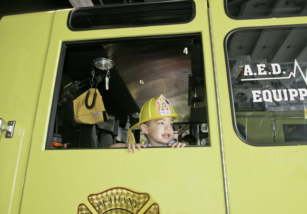 Boy sitting in a fire truck with a helmet