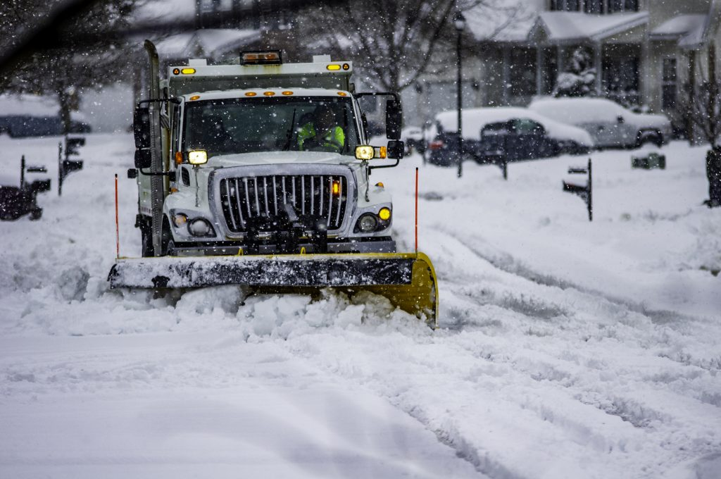 Snowplow service truck clearing residential roads of snow while flakes are still falling
